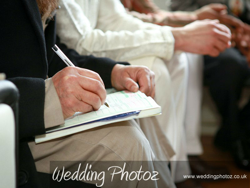 priest completing a marriage certificate
